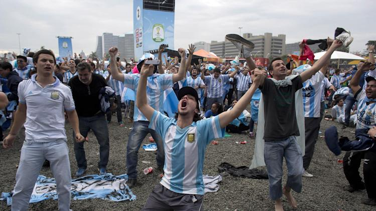 Argentine soccer fans celebrate after watching their side score a goal, via a live telecast of the World Cup group F match between Argentina and Nigeria, inside the FIFA Fan Fest area, in Porto Alegre, Brazil, Wednesday, June 25, 2014. (AP Photo/Dario Lopez-Mills)