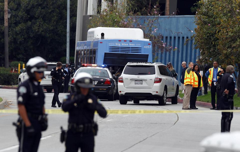 Investigators look at a Santa Monica City Bus that was shot at in Santa Monica, Calif. Friday, June 7, 2013. Someone fired gunshots near the campus of Santa Monica College shortly before noon Friday, police said, and several people were reported to be wounded. (AP Photo/Damian Dovarganes)
