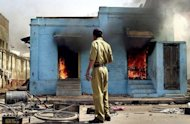 A policemn looks at burning Muslim shops at the entrance of a mosque in Ahmedabad, 28 February 2002 after Hindu activists attacked the place in revenge for the February 27 attack by a Muslim mob on a train carrying Hindu activists that left 58 people dead in the Northern state of Gujarat. Police used tear gas to control hundreds of Hindus targeting Muslim-owned shops and sparking a running street battle with police and Muslim residents. AFP PHOTO / Sebastian D'SOUZA