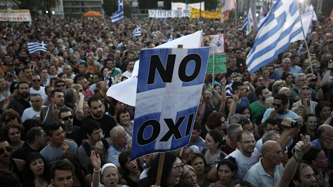 A demonstrator holds a placard reading ''NO'' during a rally organized by supporters of the No vote in Athens, Friday, July 3, 2015. A new opinion poll shows a dead heat in Greece's referendum campaign with just two days to go before Sunday's vote on whether Greeks should accept more austerity in return for bailout loans. (AP Photo/Petros Giannakouris)