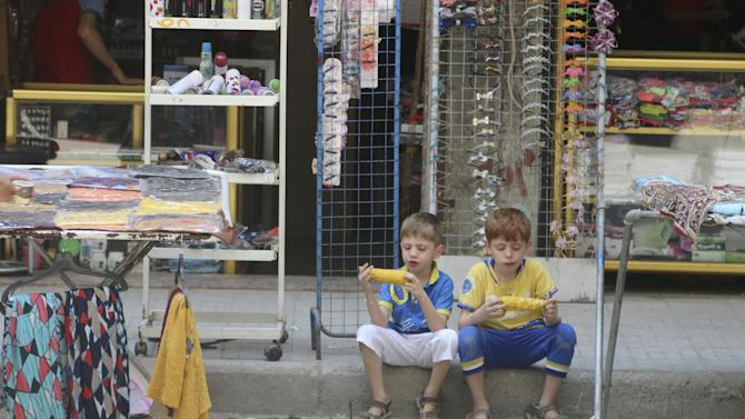 Two boys sit on a pavement as they eat corn in Aleppo's eastern district of Tariq al-Bab, Syria