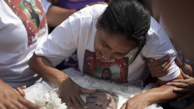 A relative mourns over the body of 14-year-old Luiza Paula da Silveira Machado during her funeral at the Jardim da Saudade cemetery in Rio de Janeiro, Brazil, Friday April 8, 2011. Brazilian families began burying the 12 children gunned down in the halls of their elementary school Thursday. Luiza is one of ten girls and two boys between the ages of 12 and 15 who were killed by 23-year-old Wellington Oliveira, who shot and killed himself after being confronted by police.  (AP Photo/Felipe Dana)