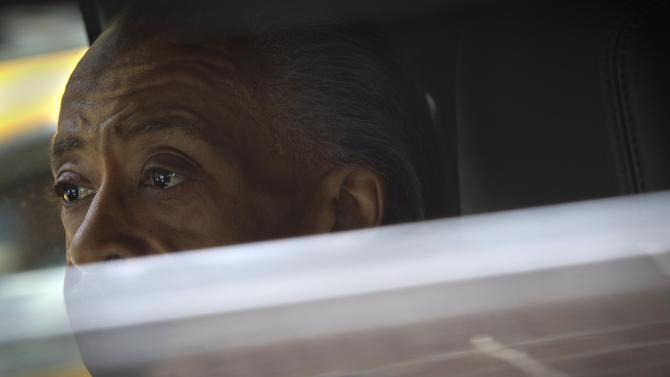 Civil rights activist Reverend Al Sharpton sits in an SUV as he leaves a news conference on a meeting he had with the Sony Pictures Co-Chairman Amy Pascal at a hotel in New York