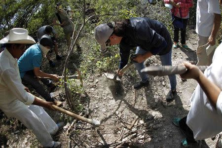 People with missing relatives dig in an area under investigation by a forensics team, near mass graves discovered in October, in La Joya on the outskirts of Iguala