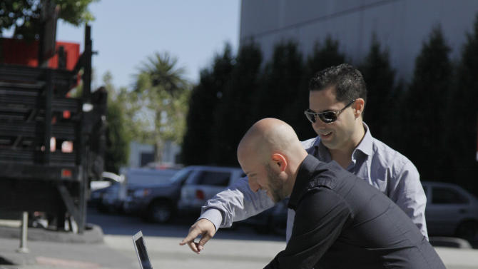 In this photo taken Tuesday Aug. 16, 2011, security consultants Don Bailey, rear, and Mathew Solnik with iSEC Partners, demonstrate with a computer how they force cars with certain alarm systems to unlock their doors and start their engines by sending them text messages in San Francisco. (AP Photo/Eric Risberg)