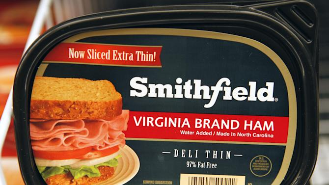 FILE- In this Wednesday, Dec. 8, 2010, file photo, Smithfield Foods products are on display at a Martins food store in Richmond, Va. Pork producer Smithfield Foods Inc. is opening a hometown restaurant to showcase its products .The company, still based in Smithfield, Va., where it was founded in 1936, opened the Taste of Smithfield on Monday, July 9, 2012, to help boost its packaged meats business. In addition to its namesake Smithfield brand, the company makes Armour and Farmland pork products. (AP Photo/Steve Helber)