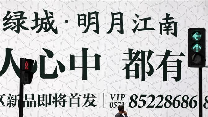 File photo of a man walking past an advertising billboard outside the Greentown residential construction site in Hangzhou