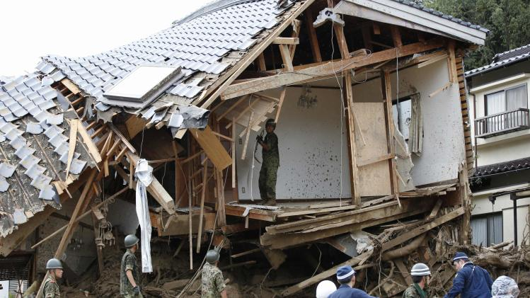 JSDF soldiers search for survivors at a site where a landslide swept through a residential area at Asaminami ward in Hiroshima