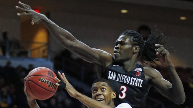 California guard Tyrone Wallace tries to shoot around San Diego State forward Angelo Chol during the first half of an NCAA college basketball game Thursday, Nov. 26, 2015, in Las Vegas. (AP Photo/John Locher)