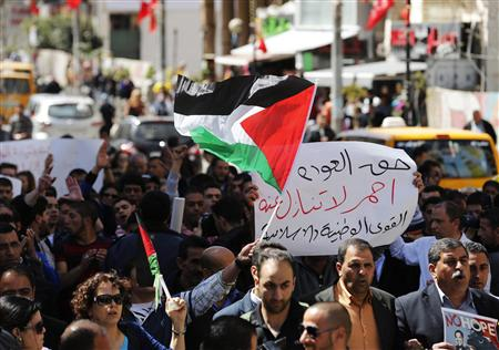 Palestinian protesters hold placards and flags during a demonstration against U.S. President Barack Obama in the West Bank city of Ramallah March 21, 2013. REUTERS/Mussa Qawasma