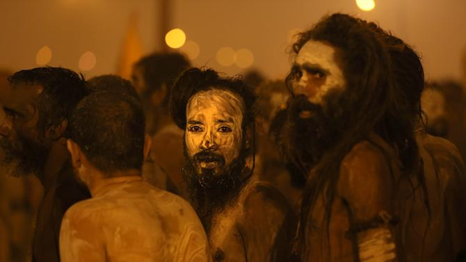 Naked Hindu holy men or a Naga Sadhus return after a dip at  Sangam, the confluence of the Rivers Ganges, Yamuna and mythical Saraswati for a dip on one of the most auspicious day Makar Sankranti,  the first day of the Maha Kumbh Mela, in Allahabad, India, Monday, Jan. 14, 2013.  Millions of Hindu pilgrims are expected to take part in the large religious congregation, which falls every 12 years and lasts for a period of over a month, during which devotees wash themselves in the waters of the Ganges believing that it washes away their sins and ends the process of reincarnation. (AP Photo /Manish Swarup)