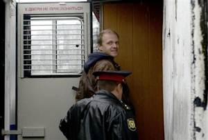 Photographer Denis Sinyakov, one of the 30 people detained after a Greenpeace protest at the Prirazlomnaya platform, is escorted to a district court building in Murmansk