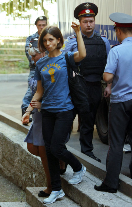 Nadezhda Tolokonnikova, left, a member of feminist punk group Pussy Riot is escorted to a court room in Moscow, Russia, Wednesday, Aug. 8, 2012. Prosecutors on Tuesday called for three-year prison sen