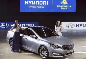 Models pose for photographs with Hyundai Motor Co's New sedan The AG at Busan International Motor Show 2014 in Busan