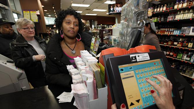 "Ceejay Johnson, 48, of Southfield, Mich., gives her Powerball ticket numbers at Andrews Downtown in Detroit, Wednesday, Nov. 28, 2012.   Tonight's Powerball total is an estimated 500 million dollar jackpot. Johnson who normally doesn't play the lottery said, ""somebodys got to win, why not me"". (AP Photo/Paul Sancya)"