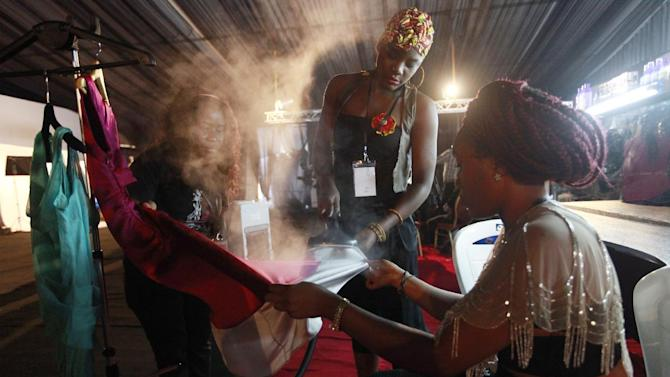 A fashion designer iron one of her dresses for presentation in the backstage during Fashion and Design Week in Lagos, Nigeria, Friday, Oct. 31, 2014. (AP Photo/Sunday Alamba)