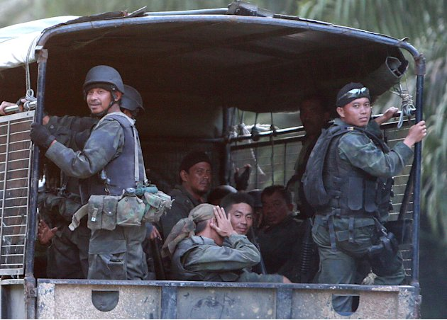 Malaysian army commandos in the back of their truck move on the way to join an assault near the area where a stand-off with Filipino gunmen took place, in Tanduo village, Lahad Datu, Borneo's Sabab st