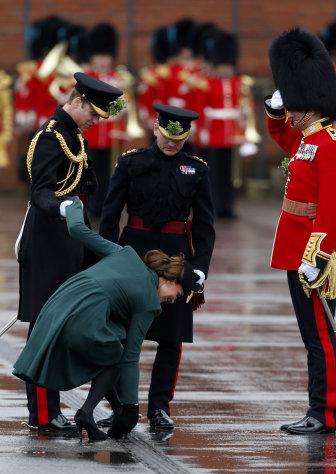 Britain&#39;s Kate Duchess of Cambridge holds onto the hand of her husband Prince William, left, as she bends down to pull the heel of her shoe out of a drainage grill after it got stuck, as she presents the traditional sprigs of shamrock to members of the 1st Battalion Irish Guards at the St Patricks Day Parade at Mons Barracks in Aldershot, England, Sunday, March 17, 2013. Kate presenting the sprigs of shamrock to the regiment Sunday, follows a century-old tradition inaugurated by Queen Alexandra, the wife of the then King, Edward VII back in 1901. (AP Photo/Matt Dunham)