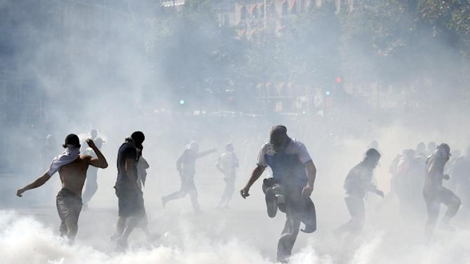 Demonstrators kick tear gas canisters as they clash with riot police in Paris on July 26, 2014 after a protest against Israel's military action in Gaza