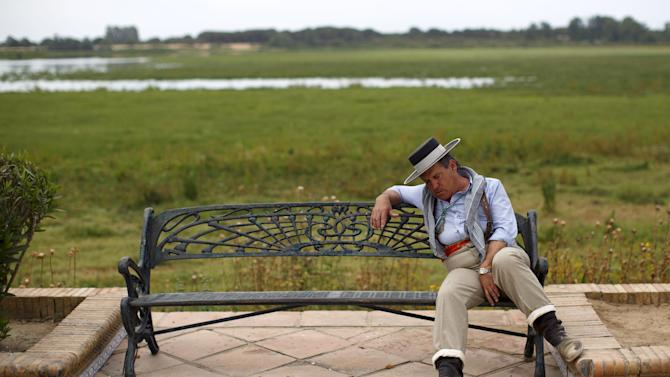 A pilgrim sleeps on a bench in the village of El Rocio in Almonte, southern Spain