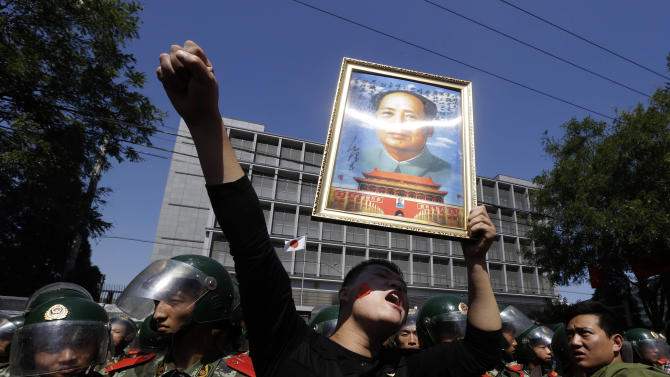 FILE - In this Sept. 15, 2012 file photo, a Chinese man holds up a portrait of former Chinese leader Mao Zedong during protests outside the Japanese Embassy in Beijing, China. The face of dissatisfaction with China's Communist Party is the face of the man synonymous with it: Mao Zedong.  Portraits of the revolutionary leader, hoisted by people born after his death 36 years ago, often led packs of demonstrators in protests over Japan's effort last week to bolster its hold on islands claimed by China.    (AP Photo/Ng Han Guan, File)