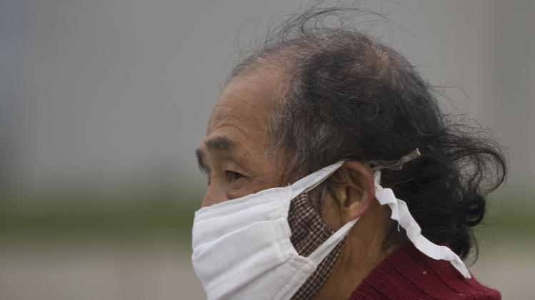 A man wears two face masks while walking on a street during a hazy day in downtown Shanghai