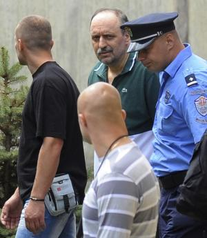 Goran Hadzic, center back in green shirt, arrives at the house where he lived before he went hiding in 2004, in Novi Sad, Serbia, Friday, July 22, 2011. Serbian authorities tracked down war crimes fugitive Goran Hadzic in the northern mountains Wednesday, arresting the last remaining fugitive sought by the U.N. war crimes court after eight years on the run. (AP Photo) SERBIA OUT