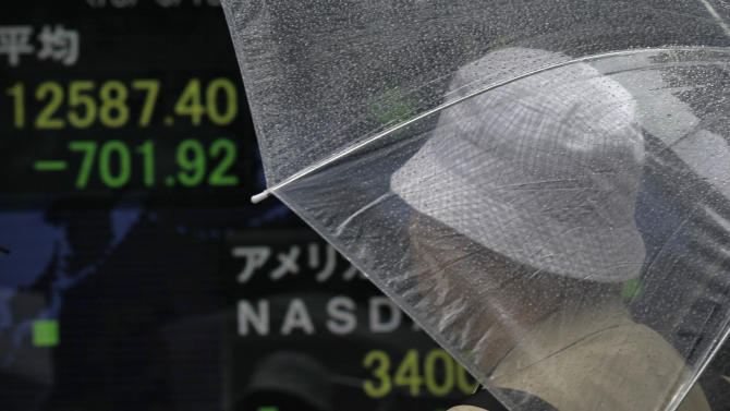 A man looks at the update of the Nikkei stock rate on an electronic board in Tokyo, Thursday, June 13, 2013. Asian stocks slid in early Thursday trading as gyrations on the Tokyo market, the region's biggest, continued, fueled by worries about a surging yen and monetary policies in the U.S. and Japan. The Nikkei 225 index, which plunged more than 6 percent earlier in the day, was 4.5 percent down by early afternoon to 12,672.70. (AP Photo/Junji Kurokawa)