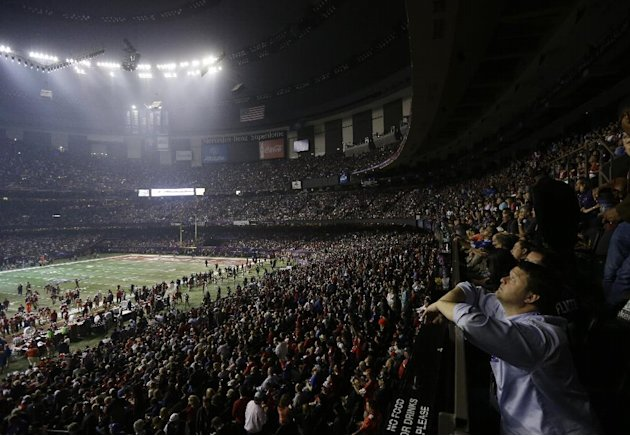 Fans and members of the Baltimore Ravens and the San Francisco 49ers wait for power to return in the Superdome during an outage in the second half of the NFL Super Bowl XLVII football game, Sunday, Fe
