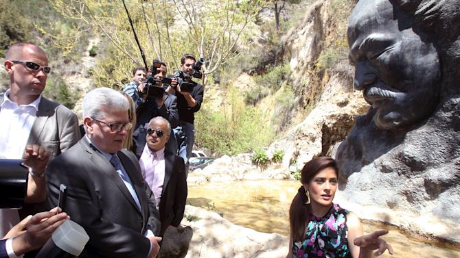 """Actress Salma Hayek stands near a statue of late writer Khalil Gibran during a visit to promote her film """"The Prophet"""" in Gibran's hometown of Bcharre, Lebanon"""