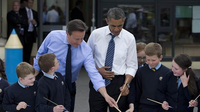 President Barack Obama and British Prime Minister David Cameron help students paint a mural during a visit to the Enniskillen Integrated Primary School in Enniskillen, Northern Ireland, Monday, June 17, 2013. The visit takes place before leaders from the G-8 nations are to gather to discuss the ongoing conflict in Syria, and free-trade issues. (AP Photo/Evan Vucci)