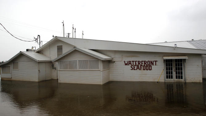 The Waterfront Seafood company is flooded as water covers Shell Belt Road in Bayou La Batre, Ala.  on Tuesday, Aug. 28, 2012.  The U.S. National Hurricane Center in Miami said Isaac became a Category 1 hurricane Tuesday with winds of 75 mph. It could get stronger by the time it's expected to reach the swampy coast of southeast Louisiana. (AP Photo/Butch Dill)