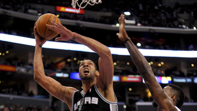 San Antonio Spurs forward Tim Duncan (21) gets by Los Angeles Clippers center DeAndre Jordan (6) for a basket in the first half of a NBA basketball game, Tuesday, Feb. 18, 2014, in Los Angeles.(AP Photo/Gus Ruelas)