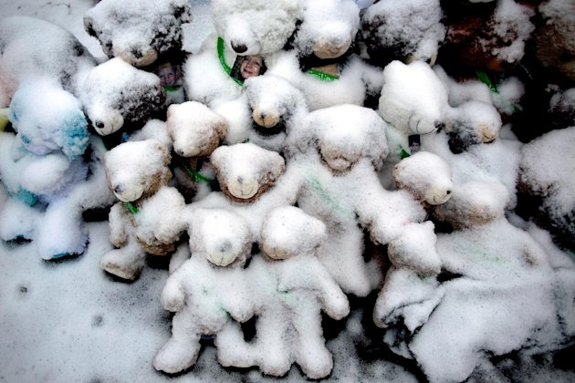Snow-covered stuffed animals with photos attached sit at a memorial in Newtown, Conn. Tuesday, Dec. 25, 2012. People continue to visit memorials after gunman Adam Lanza walked into Sandy Hook Elementa