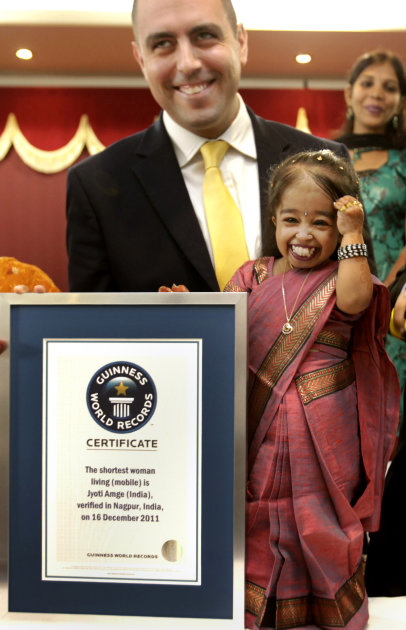 Jyoti Amge smiles after getting the title of the shortest woman by the Guinness World Records adjudicator Rob Molloy, in Nagpur, India, Friday, Dec. 16, 2011. Amge was declared the shortest woman in t
