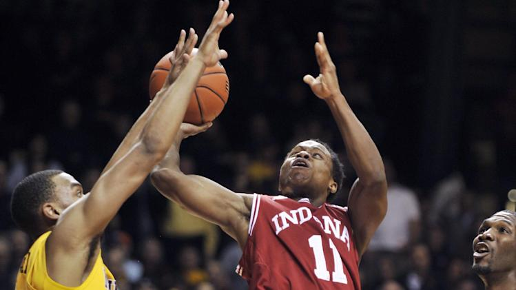 Indiana's Kevin Ferrell (11) gets off a shot over Minnesota's Andre Hollins, left, during the first half of an NCAA college basketball game, Tuesday, Feb. 26, 2013, in Minneapolis. Minnesota's Trevor Mbakwe is at right. (AP Photo/Tom Olmscheid)