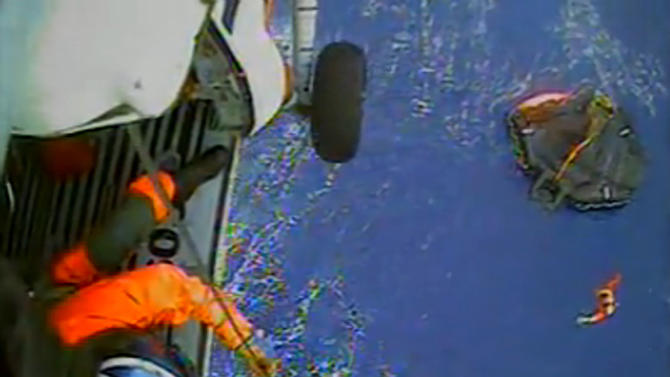 FILE - In this Monday, Oct. 29, 2012 file photo made from video and provided by the U.S. Coast Guard, a USCG rescue swimmer, in water at right, and a crew member use a hoist to bring up survivors into a helicopter, off the North Carolina Coast. Fourteen crew members of a replica 18th Century tall ship that sank during Hurricane Sandy owe their lives in part to a pair of Coast Guard rescue swimmers who dared 50-mile-an-hour winds and 18-foot waves in the open ocean. Their bravery was moulded at the Coast Guard's only training school for rescue swimmers, which just added a multi-million-dollar facility to simulate crises that call them to action. (AP Photo/U.S. Coast Guard, File)