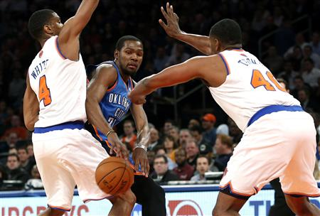Oklahoma City Thunder forward Durant passes between New York Knicks' Thomas and White during their NBA basketball game in New York
