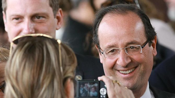 French Socialist Party candidate for the presidential election Francois Hollande reacts as he poses for a picture in the market in Tulle, southwestern France, Saturday, May 5, 2012. The second round of the French presidential elections will take place on May 6, 2012. (AP Photo/Bob Edme)