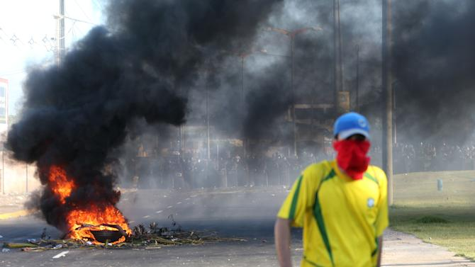 A masked protestor walks near a burning barricade as riot police stand guard near the Castelao stadium in Fortaleza, Brazil, Wednesday, June 19, 2013. Protesters cut off the main access road to the stadium where Brazil goes up against Mexico in the Confederations Cup soccer tournament. Beginning as protests against bus fare hikes, the demonstrations have quickly ballooned to include broad middle-class outrage over the failure of governments to provide basic services and ensure public safety. (AP Photo/Andre Penner)