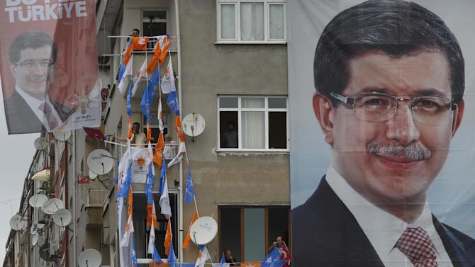 A banner with the picture of Turkey's Prime Minister and leader of the Justice and Development Party (AKP) Ahmet Davutoglu, covers a building as supporters of the party listen to his speech during a rally in Istanbul, Turkey, ahead of the upcoming June 7, 2015 general election, Tuesday, June 2, 2015. The overarching drama of the election has been whether Turkey's President Recep Tayyip Erdogan's AKP party will win a strong enough majority to change the constitution and put Erdogan at the unquestioned pinnacle of Turkish politics in a new presidential system. (AP Photo/Lefteris Pitarakis)