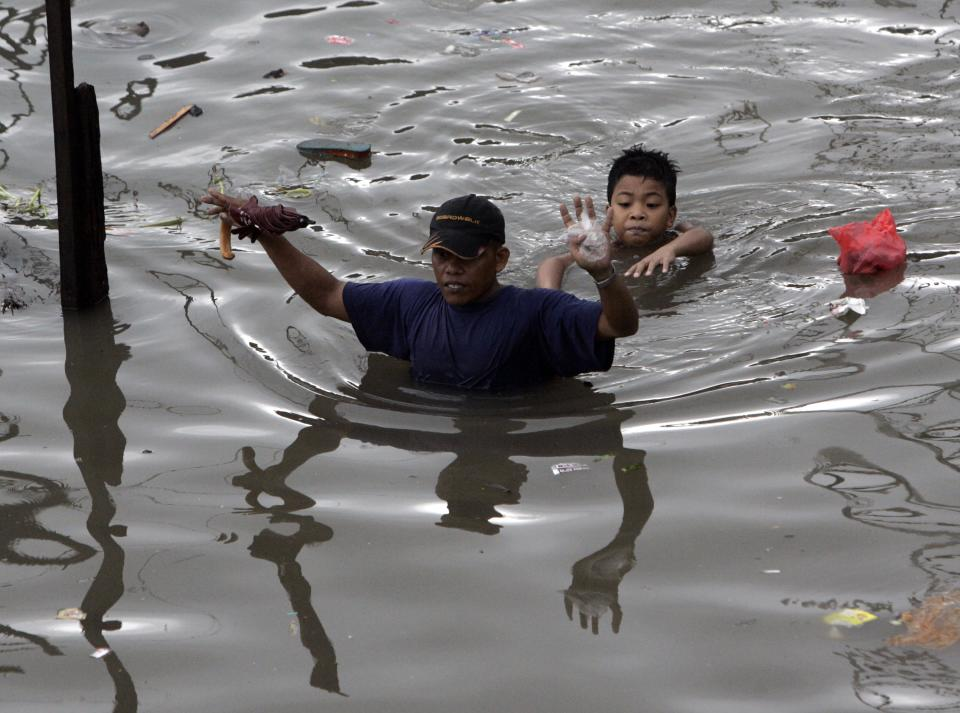 A man wades through a chest deep flood water as a young boy tries to catch up with him Tuesday, Aug. 2, 2011 in suburban Quezon City, north of Manila, Philippines.  A powerful typhoon is blowing away from the northern Philippines after killing at least four people even though it did not make landfall. (AP Photo/Pat Roque)