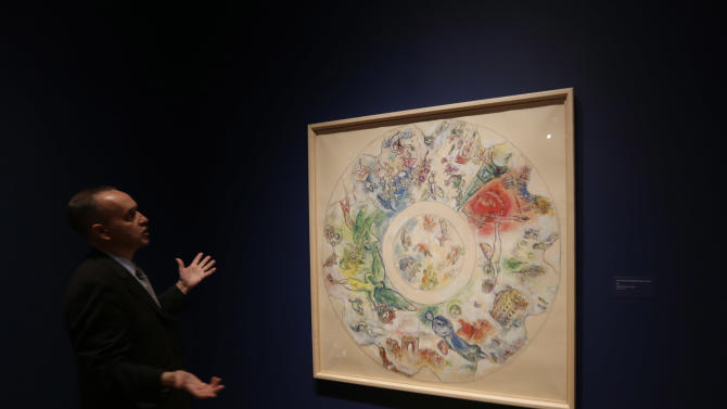 "In this photo taken Feb. 13, 2013 Museum curator Olivier Meslay talks about a 1963 Marc Chagall  piece titled ""Final study for the ceiling of the opera Garnier,"" included in the ""Chagall: Beyond Color,"" exhibit during a preview at the Dallas Museum of Art in Dallas.  This will be the only U.S. venue to host the exhibit that opens to the public on Sunday. (AP Photo/LM Otero)"