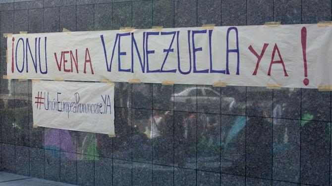 """A banners is posted on the wall of the United Nations offices in Caracas, Venezuela, Tuesday, March 25, 2014. The banners reads in Spanish """"UN come to Venezuela now"""" and the one below reads """"European Union pronounce yourself"""". A large group of protesting anti-government students have camped in front of the office of the United Nations asking it to come and observe the situation, as Venezuela's bloody political standoff heads into its third month. The decision to pitch tents on the concrete sidewalk along one of Caracas' busiest, smog-filled streets comes as foreign ministers from several South American nations arrive Tuesday to lend support to President Nicolas Maduro's efforts at reconciliation with his opponents. (AP Photo/Fernando Llano)"""