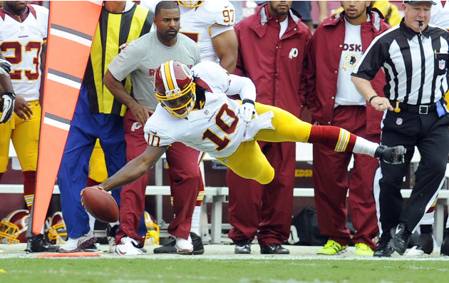 Washington Redskins quarterback Robert Griffin III dives for a first down during the first half of an NFL preseason football game against the Indianapolis Colts on Saturday, Aug. 25, 2012, in Landover