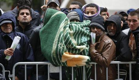 Migrants queue outside Office of Health and Social Affairs as they wait to register in Berlin