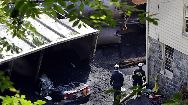 Officials walk past a car that was destroyed by a CSX freight train that derailed while hauling coal overnight in Ellicott City, Md., Tuesday, Aug. 21, 2012. Authorities said two people not employed by the railroad were killed in the incident. (AP Photo/Patrick Semansky)