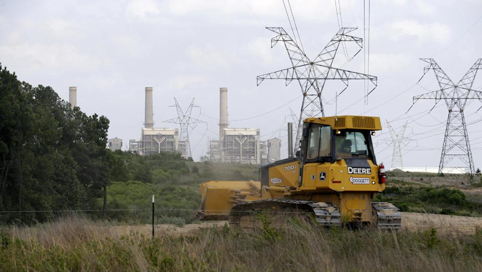 In this July 29, 2013, photo, a bulldozer works on a Luminant Mining Co. expansion project near Tatum, Texas. Decades of mining and power plant activity that helped East Texas towns grow and thrive could be threatened as a large energy provider faces possible bankruptcy. (AP Photo/LM Otero)