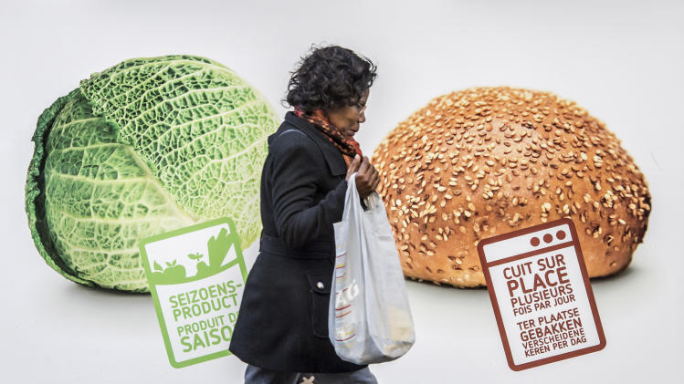 A woman walks by an advertisement for vegetables and bread in Brussels on Thursday, Nov. 22, 2012. As leaders from the 27-nation European Union gather in Brussels to debate the organization's budgets for the years 2014-2020, they'll talk not only about economic growth but crop growth, as well. Fully 41 percent of the EU's budget goes to agriculture. Signs read from left to right, 'Seasonal Products' and 'freshly baked several times a day'. (AP Photo/Geert Vanden Wijngaert)