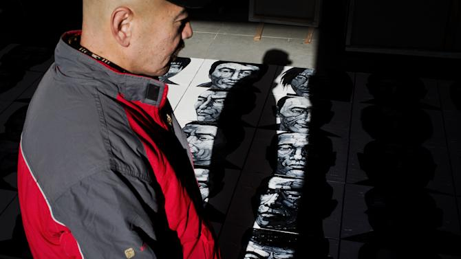In this photo taken on Tuesday, Dec. 25, 2012, Beijing-based artist Liu Yi looks at his works of portraits of Tibetans who have self-immolated over the past three years, at his studio in Songzhuang art village in Tongzhou, on the outskirt of Beijing. Liu is working on a series of black-and-white portraits he knows will never be shown in a Chinese gallery. His varied subjects - men and women, young and old, smiling and pensive - have one thing in common: They are Tibetans who have set themselves on fire to protest repressive Chinese rule. (AP Photo/Andy Wong)